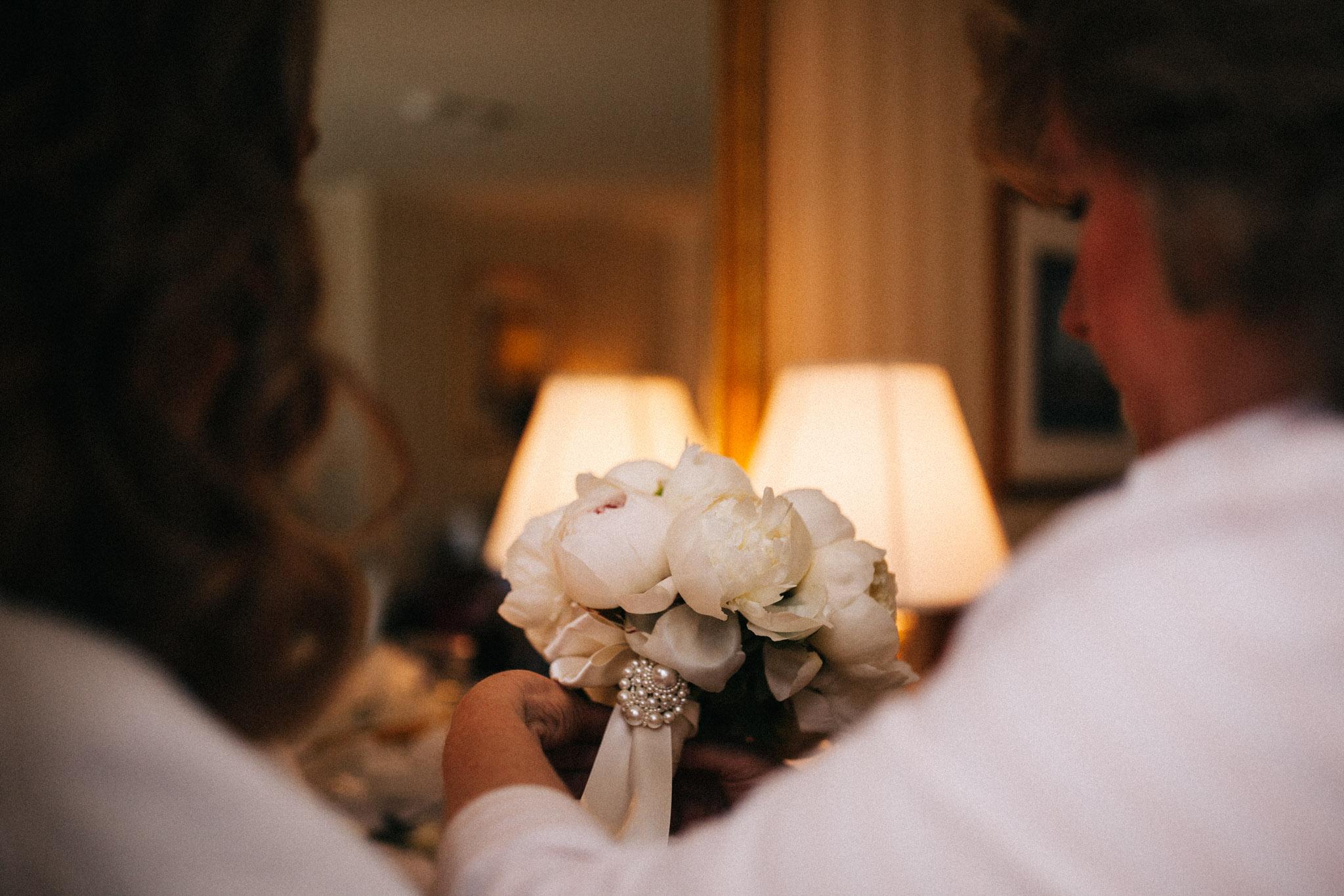 mother handing bride flowers