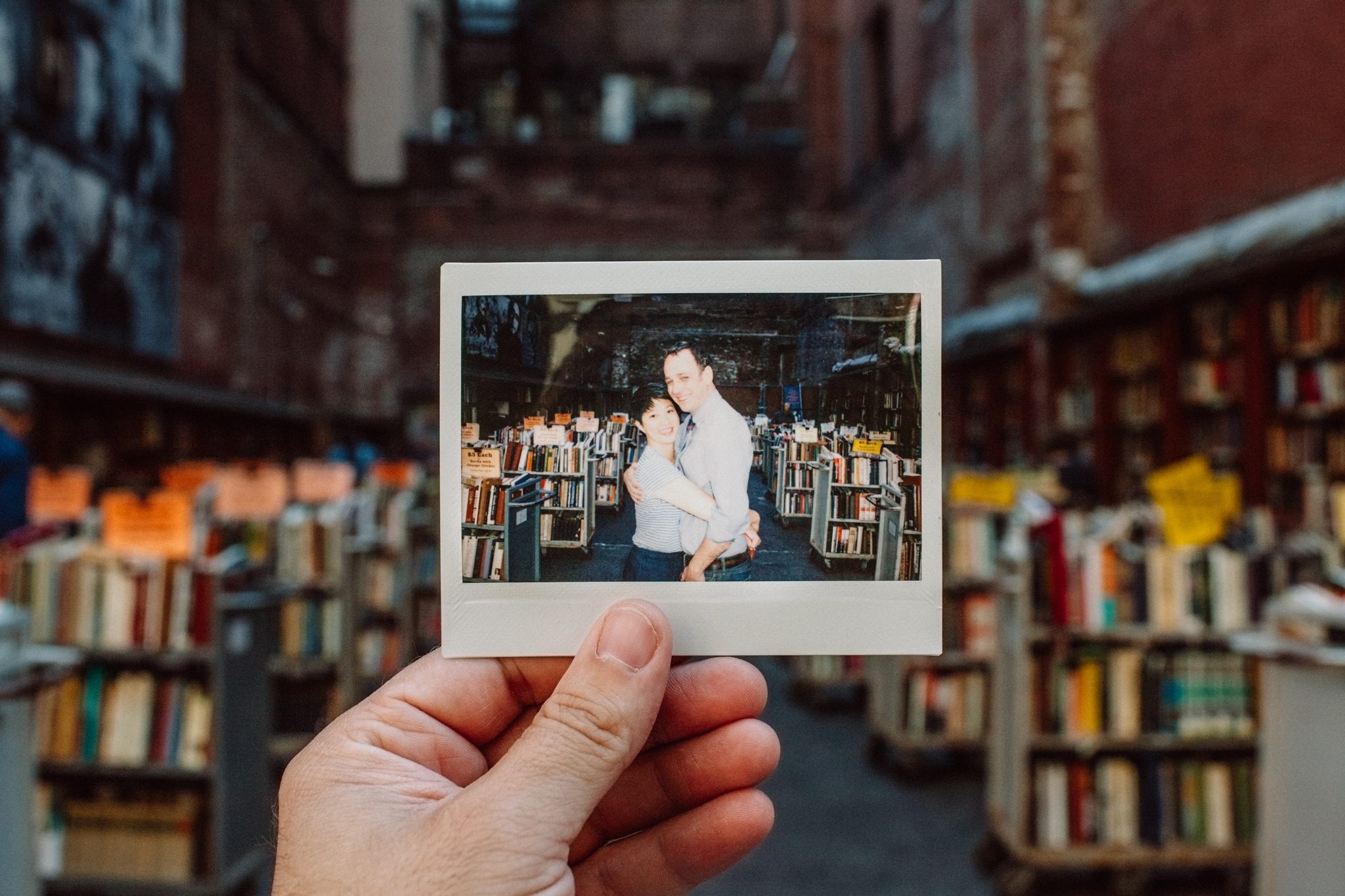 man holding instax photo for boston bookstore engagement session