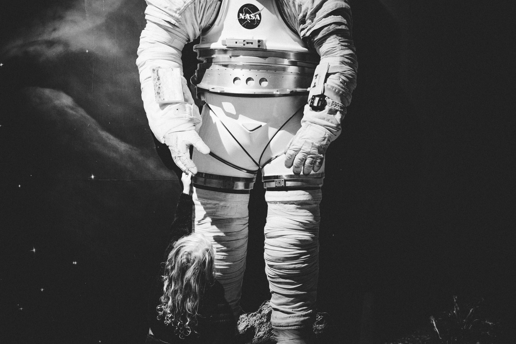 girl holds astronauts hand