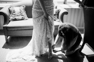 bride putting shoes on before the wedding