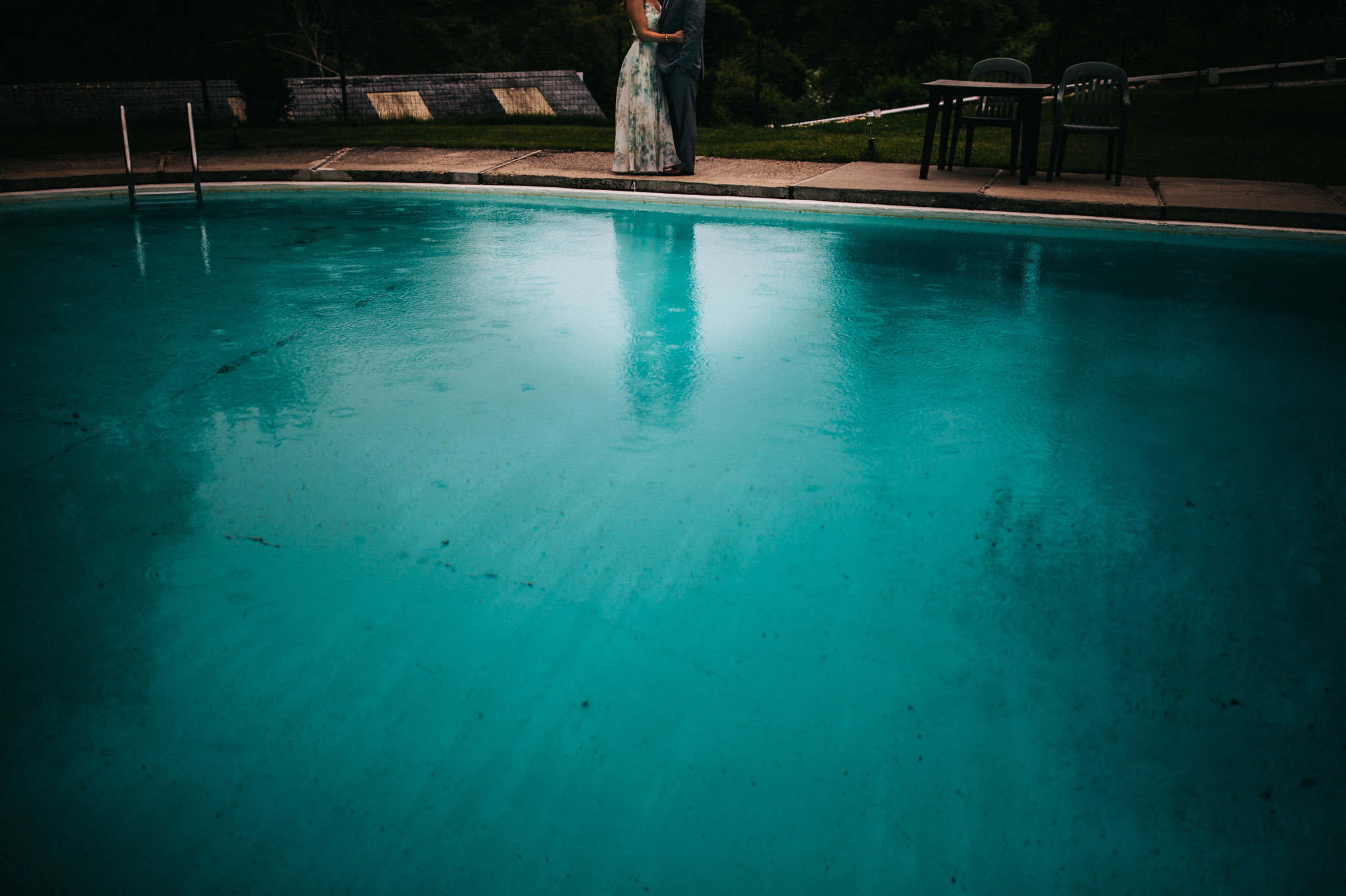 bride and groom ready to swim in the rain